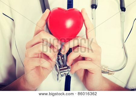 Red heart held by a female doctor. Close up.