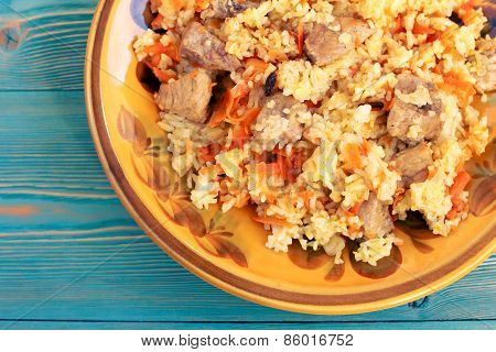 Pilau from rice, meat, carrot and barberry in yellow plate