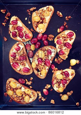Toasts with ricotta, baked grapes, walnut on baking, toned