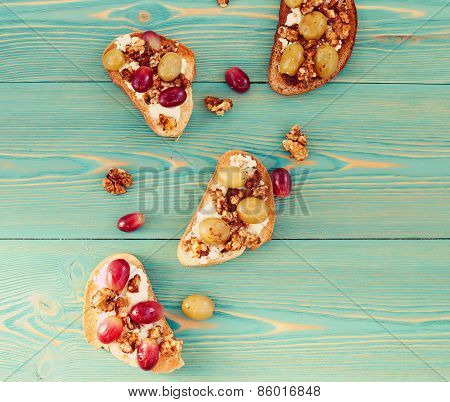 Toasts with baked grape and ricotta on blue wooden table