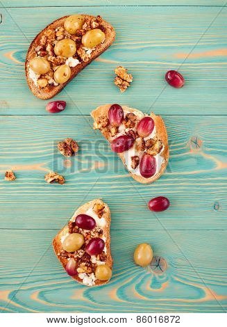 Rye and wheat toasts with baked grape on blue table