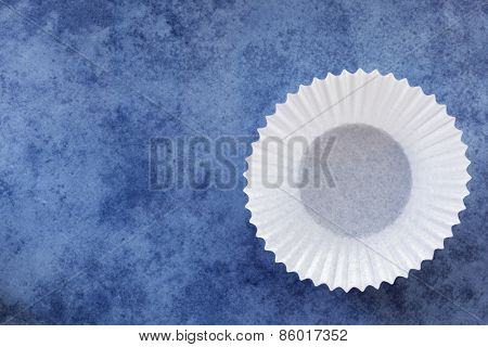 Empty white paper cupcake case over textured blue background.  Overhead view.
