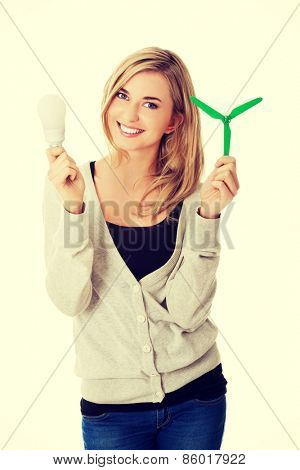 Green energy concept. Woman with led light bulb and windmill