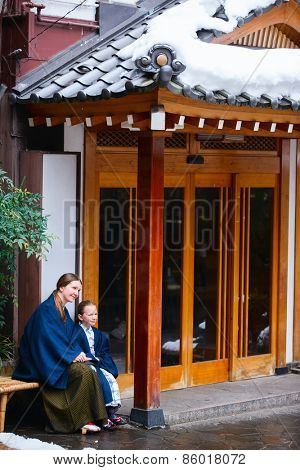 Family of mother and daughter wearing yukata traditional Japanese kimono at street of onsen resort town in Japan.