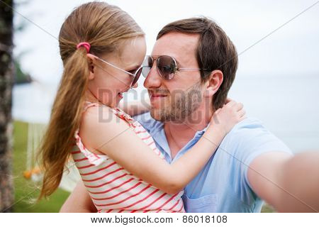 Happy family father and his adorable little daughter at beach making selfie
