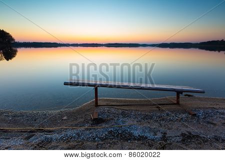 Lake Landscape At Sunset With Bench