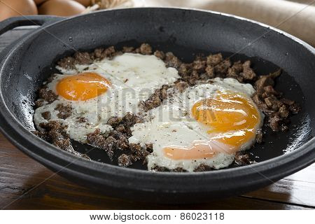 Braised beef with egg on iron cast pan close up