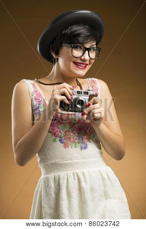 Vintage girl taking pictures using an old camera in a beige background