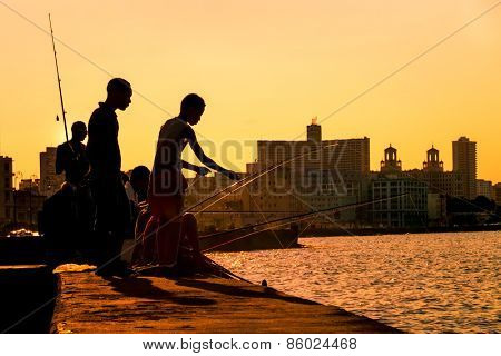 HAVANA - MARCH 19, 2015 : Silhouette of young boys fishing at sunset at the Malecon seawall in Havana