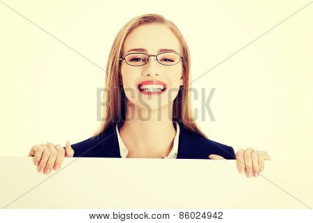 Smiling young businesswoman showing blank signboard