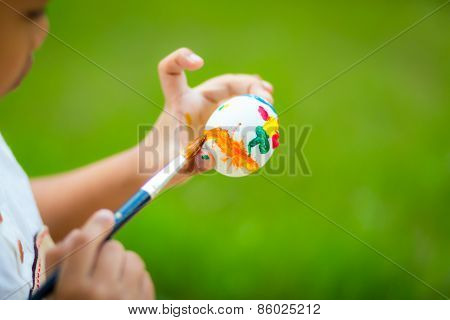 Child painting easter egg with paintbrush
