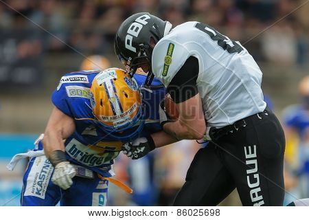 GRAZ, AUSTRIA - APRIL 04, 2014: WR Martin Sindler (#81 Panthers) is tackled by DB Dominik Poetsch (#3 Giants) in an AFL football game.