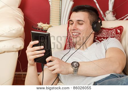 Young Handsome Man Listening To Music Via Tablet