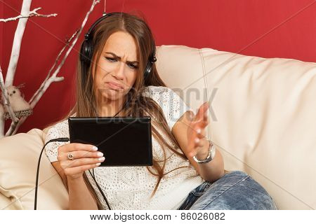 Young Woman Listening To Music Via Digital Tablet And Has A Problem