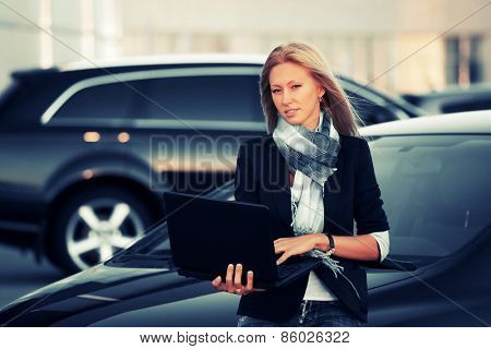 Young fashion business woman with laptop by her car