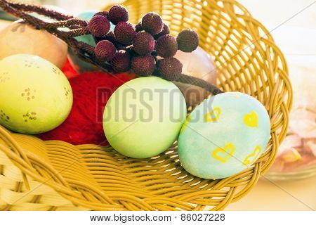 Easter eggs in a basket with a branch in the morning, soft light