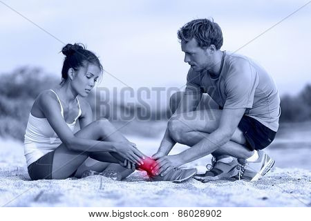 Sprained ankle - trainer helping runner in pain. Woman athlete having running accident during marathon, with painful leg sprain being helped by personal coach or medic. Two active adults on beach.