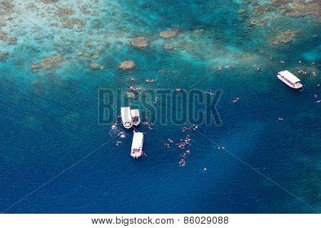 Above aerial view of tropical ocean, boats and tourists snorkelling at reef in Palau