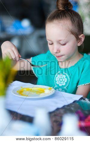 Adorable little girl eating breakfast in restaurant