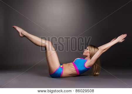Image of graceful blonde doing pilates exercise