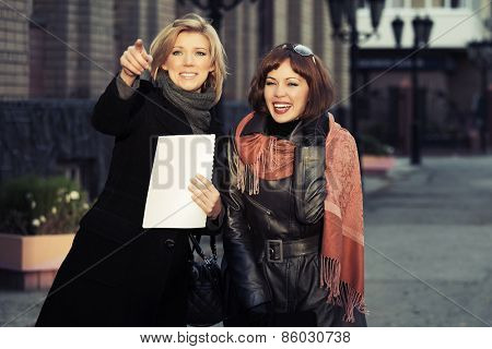 Two happy young fashion women on a city street