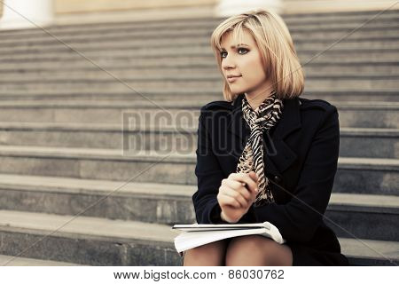 Fashion business woman with notebook sitting on the steps