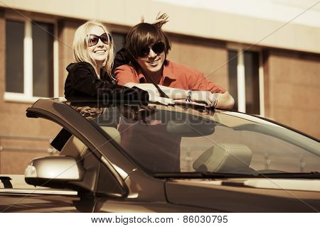 Happy young fashion couple in a convertible car