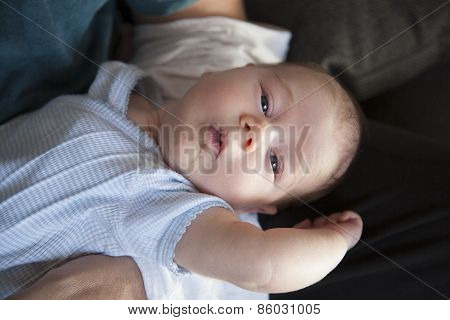 Newborn On Man Arms Looking