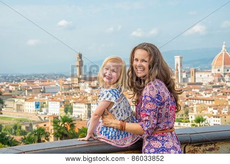 Portrait Of Happy Mother And Baby Girl Against Panoramic View Of Florence, Italy