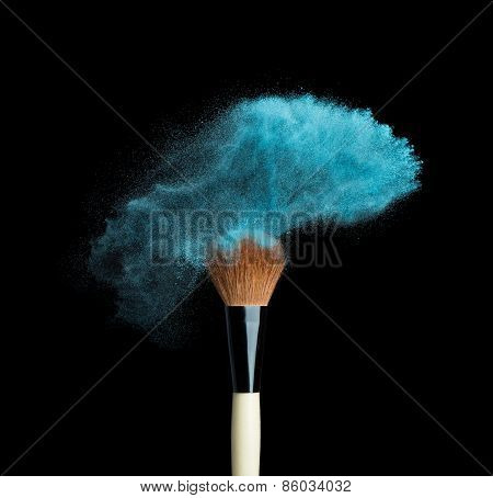 Isolated blue make-up powder with brush on black background