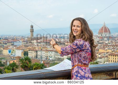 Young Woman With Map Pointing On Panoramic View Of Florence, Italy
