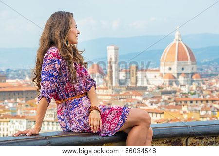 Young Woman Sitting Against Panoramic View Of Florence, Italy An
