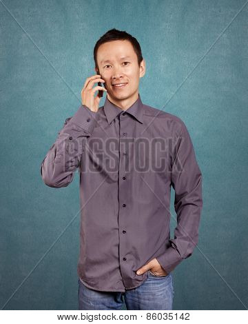 Asian man smiling, looking on camera, talking on the cell