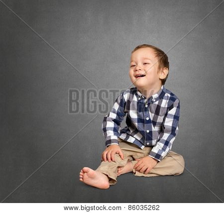 Cute boy siting on the floor and smiling