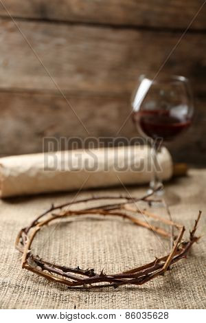 Crown of thorns, scroll and glass of wine on old wooden background