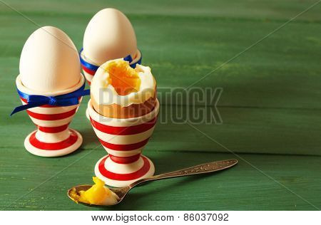 Boiled eggs in holders on color wooden background