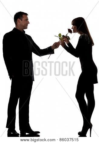 one  lovers couple man offering rose flower and woman smelling in studio silhouette isolated on white background