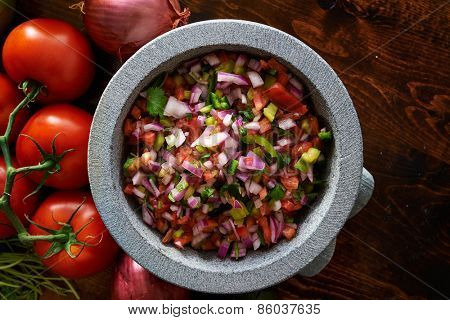 fresh mexican pico de gallo salsa in stone molcajete shot top down