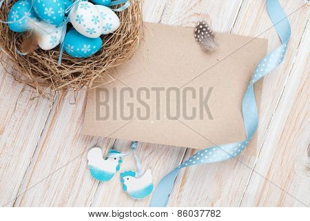 Easter greeting card with blue and white eggs in nest and decor. Top view with copy space