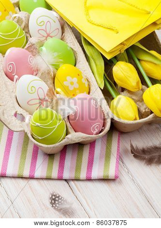 Easter with yellow tulips, colorful eggs and gift bag. Top view