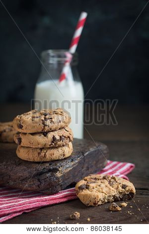 chocolate chip cookies and milk on a wooden table