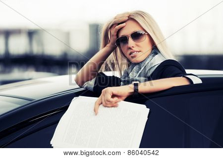 Fashion business woman with financial papers by her car