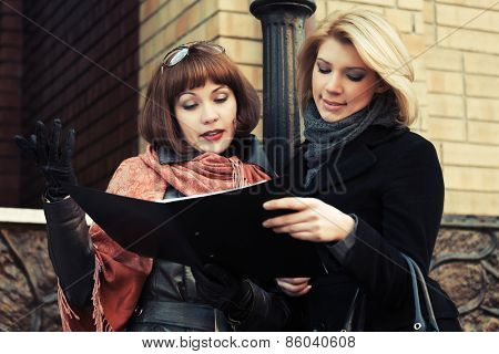 Two young fashion business women with a folder at office building