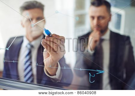 One man explaining graph to another person