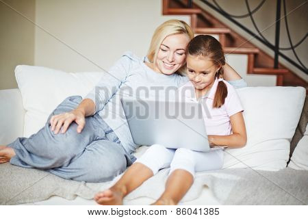 Smiling mother and daughter using laptop at home
