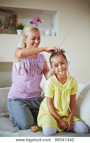 Mother making hairstyle for her daughter