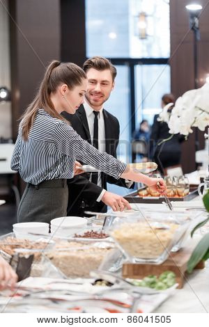 Business professionals by the buffet table