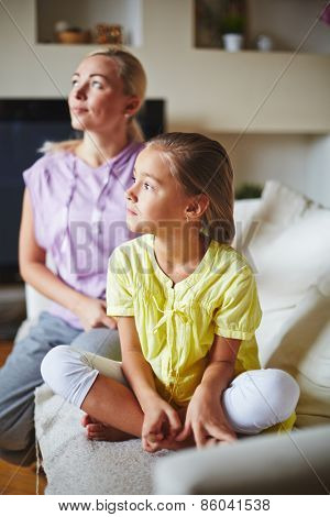 Two members of family looking at sideway and sitting on sofa