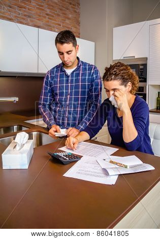 Unemployed husband reviewing the bills and wife crying by debts