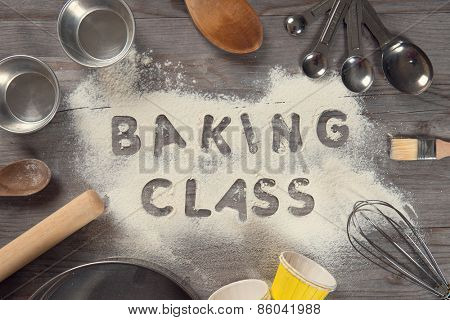 Word baking class written in white flour on a old wooden table from top view in vintage tone, surrounding by baking tools.